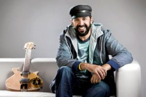 Juan Luis Guerra sitting on couch and guitar next to him