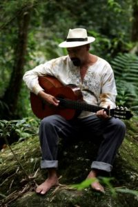 Andres Jimenez playing guitar on mountain